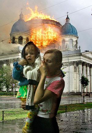 Una mujer con un niño en brazos pasa por delante de la catedral en llamas. (Foto: AP)