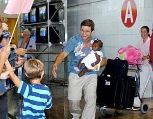 El matrimonio formado por Javier Torrente y Natalia Castellanos es recibido por sus hijos Marc y Víctor al llegar al aeropuerto del Prat. (Foto: EFE)