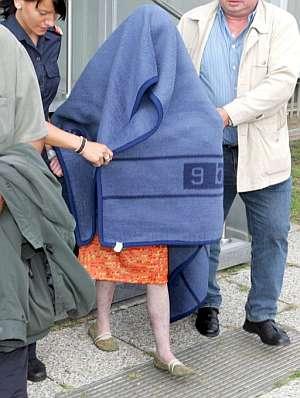 Natascha Kampusch, tapada con una manta y escoltada por la Policía. (Foto: EFE)