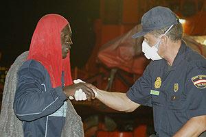 Uno de los inmigrantes llegados a Tenerife anoche, ayudado por un policía nacional. (Foto: AFP)