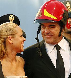 Oliver Stone (con casco de bombero) y Maria Bello, una de las protagonistas de 'World Trade Center', en Venecia. (Foto: AP)