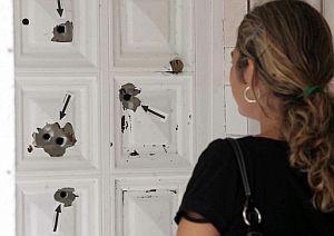 Una joven observa los impactos de bala, señalados por la Policía con flechas, en una puerta afectada por el tiroteo. (Foto: EFE)
