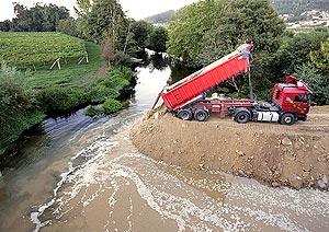 Un camión arroja arena al curso del río para retener el vertido. (Foto: EFE)
