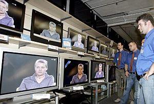 Empleados de unos almacenes, durante la emisión de la entrevista. (Foto. EFE)