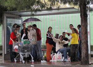 Unos jóvenes hacen 'botellón' bajo una marquesina en Sevilla. (Foto: Esther Lobato)