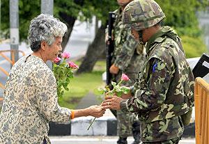 Una mujer lleva rosas a los soldados golpistas en Bangkok. (Foto: REUTERS)