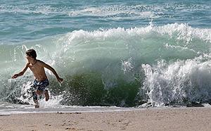 Un joven bañista en la playa del Orzán en La Coruña. (Foto: EFE)
