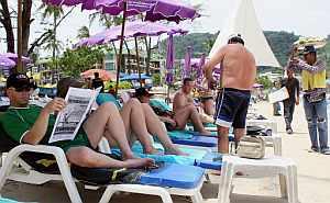 Un turista lee el periódico en una playa tailandesa. (Foto: AFP)