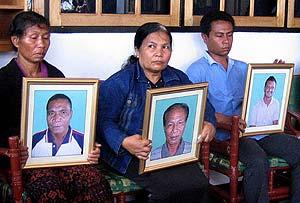 Familiares de los tres ejecutados portan sus retratos en su memoria. (Foto: AP)