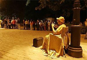 Un figurante ameniza la espera en las colas del Prado. (J. Martínez)