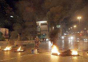 Un soldado libanés junto a neumáticos ardiendo en el centro de Beirut. (Foto: EFE)