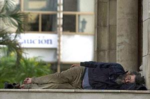 Un indigente duerme en uno de los soportales del Palacio de Justicia de la capital tinerfeña. (Foto: EFE)