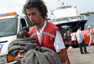Un voluntario de Cruz Roja traslada a un bebé. (Foto: Antonio Meres)