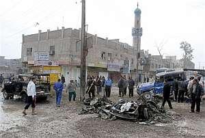 Varios iraquíes observan los restos del coche bomba. (Foto: AP)