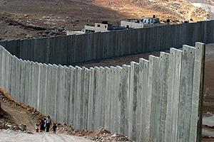 Palestinos caminan junto al muro en Abu Dis. (Foto: EFE)