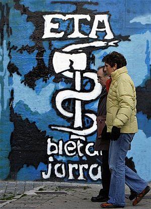 Una pareja camina junto a un muro de Alsasua con el anagrama de ETA. (Foto: AP)