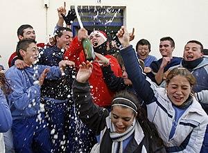 Un grupo de alumnos de una escuela taller y vecinos de Santiponce (Sevilla) celebran el Gordo. (Foto: EFE)
