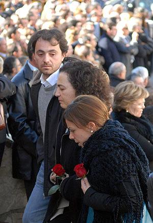 Familiares del fallecido con una rosa roja en sus manos. (Foto: EFE)