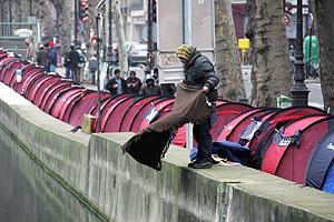 Un 'Sintecho' sacude una manta en el canal al lado de la fila de tiendas. (Foto: AFP)