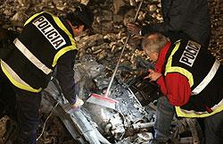 Bomberos y policías examinan uno de los coches estacionados en el aparcamiento. (Foto: EFE)