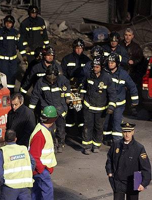 Un grupo de bomberos traslada el cuerpo de Palate. (Foto: EFE)