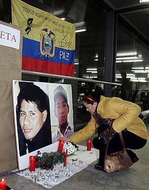 Una mujer enciende una vela en el panel instalado en la T4 con fotografías de los dos desaparecidos. (Foto: EFE)