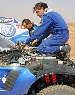 Sainz intenta solucionar el fallo eléctrico, con ayuda del portugués Sousa. (Foto: AFP)