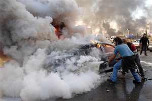 Dos hombres tratan de apagar un coche incendiado. (Foto: AP)