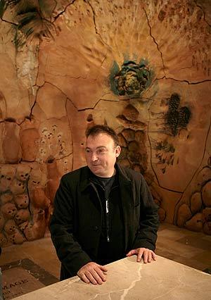 El pintor posa junto a su retablo, que tardó siete años en concluir. (Foto: AFP)