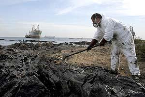 Un operario limpia el vertido de Algeciras. (Foto: EFE)