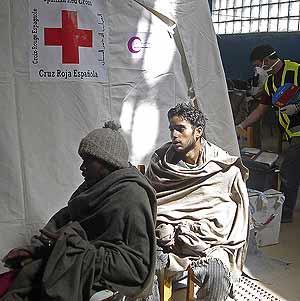 Algunos de los inmigrantes, atendidos por Cruz Roja. (Foto: EFE)