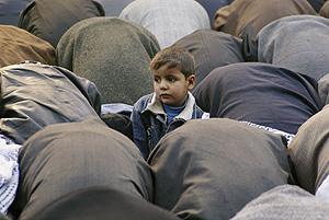 Un niño, de pie en medio de un grupo de musulmanes rezando. (Foto: REUTERS)