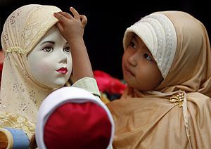 Una niña malasia juega con un pañuelo. (Foto: REUTERS)