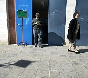 Dos votantes salen de uno de los centros electorales en Sevilla. (Foto: AFP)
