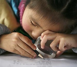 Un niño ciego con problemas de visión lee con una lupa. (Foto: REUTERS)