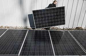 Un hombre transporta unas placas solares. (Foto: Reuters)