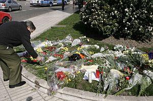 Un hombre deposita un ramo de flores en la plaza de la República Dominicana de Madrid. (Foto: EFE)
