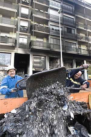 Unos obreros retiran escombros del edificio de viviendas afectado por el ataque. (Foto: Mitxi)
