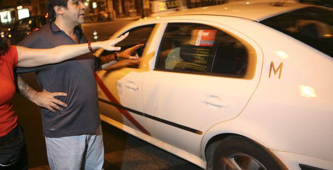 Una pareja intenta coger un taxi, de noche. (Foto: Antonio M. Xoubanova)