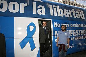 Ángel Acebes y el presidente de Nuevas Generaciones, Nacho Uriarte, ante el autobús que recorre Madrid para informar de las manifestaciones. (Foto: EFE)