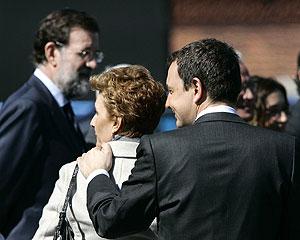 El presidente del Gobierno y su mujer, ambos de espaldas, pasan cerca de Mariano Rajoy. (Foto: EFE)