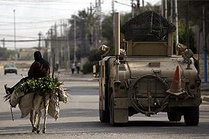 Una mujer pasea con su burro al lado de un vehículo de EEUU en el sur de Bagdad. (Foto: AFP)