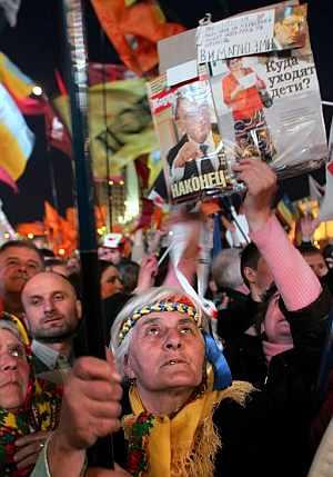 Seguidores de la líder de la oposición de Ukrania Julia Timoshenko escuchan su discurso el sábado en las calles de Kiev. (Foto: EFE)