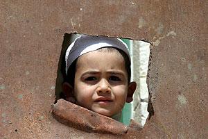 Un niño palestino mira por un hueco el control policial llevado a cabo en la ciudad de Hebrón. (Foto: EFE)