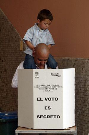 Un ecuta junto a su hijo en una mesa electoral. (Foto: AFP)