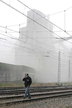 Un hombre camina junto a una planta de carbón en la cuenca del Nalón. (Foto: EFE)