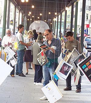 Transeúntes con los 'Libros colgantes' de la calle Fuencarral. (Foto: Miguel A. Ortega).