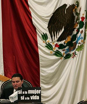 El senador antiabortista Jacobo Bonilla, muestra un cartel en la Asamblea en contra de la medida. (Foto: AP)