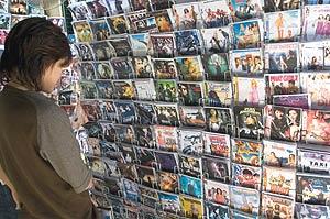 Una chica observa varios DVD piratas en un mercado de Vientiane (Laos). (Foto: EFE)