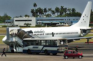 Vista del ómnibus secuestrado y del avión que intentaban abordar los reclutas. (Foto: EFE)